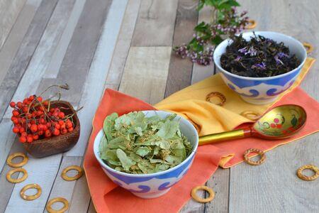 Various herbal tea ingredients (linden tea, blooming sally, mint, rowan berries) over wooden board background