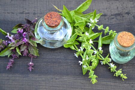 Oil with green and purple blooming basil close-up in a bottle on a wooden table in russian style Stok Fotoğraf