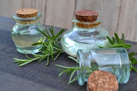 Rosemary essential oil in glass bottles with cork stoppers and fresh rosemary herb on wooden rustic background Stok Fotoğraf