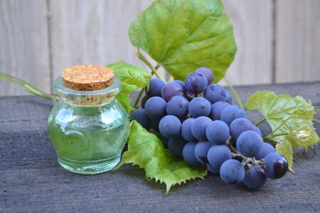 Essential oil of grape, vine, blue grapes, old wooden background in russian style