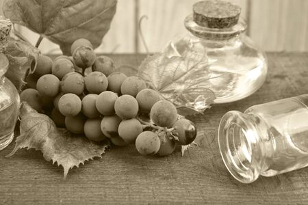 Bottle with grape seed oil on rustic background. Monochrome photo. Fruit, antioxidant. Stok Fotoğraf
