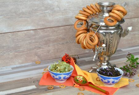 Appetizing tasty bagels on the traditional russian samovar with linden and mint herbal tea
