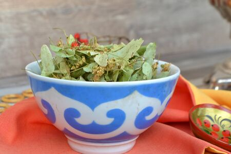 Linden flowers and leaves in pot (dry herbal tea)  on a wooden background.