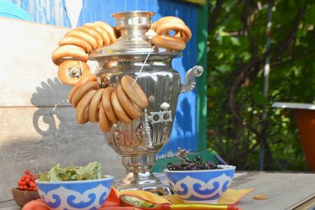 Russian traditional samovar with colorful donuts and bagels with herbal tea on a wooden shabby background 写真素材