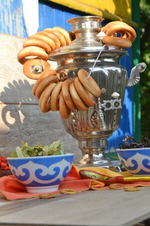 Metal old traditional russian samovar for tea drinking. Brewing tea with a bunch of sushiks, bagels, snack, vertical photo