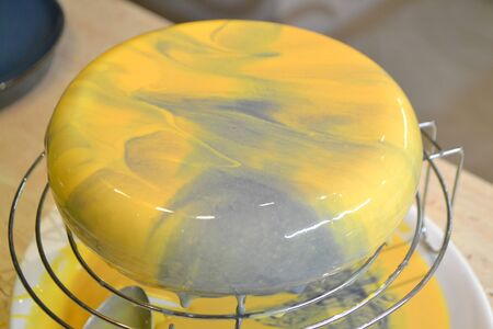 Process of decorating cake with mirror glaze. The girl creates a drawing of mousse on the cake. Frozen mirror icing on the cake.
