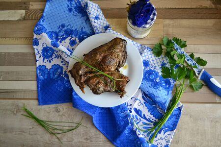 Hunting cuisine. Hare (or rabbit)  slices with spices on gzhel napkin, russian style Фото со стока