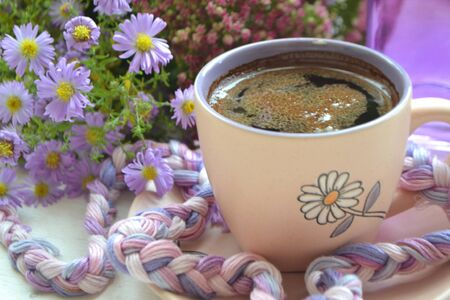 cup of coffee next to autumn purple flowers on wooden texture. Banco de Imagens