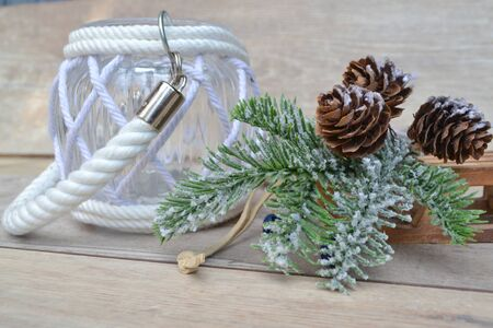 Christmas decorations cones and sled on shabby table in grey and white tones