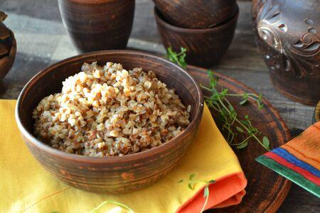 Buckwheat porridge in ceramic bowl on a rustic wood background