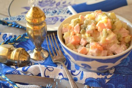 Traditional Russian cuisine: Olivier salad. White and blue colors of design of festive table in gzhel style