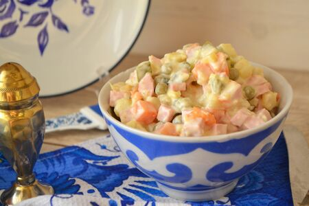 Traditional Russian salad Olivier in blue white bowl in gzhel style Stock Photo