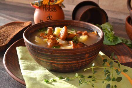 Mushroom cream chanterelle soup in brown rustic bowl close up.
