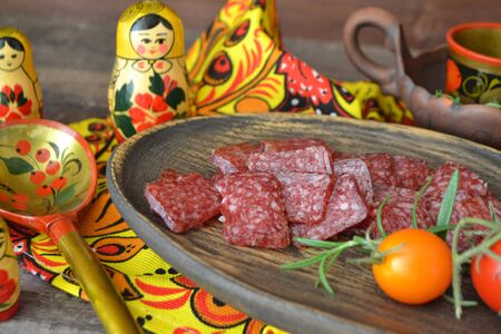 Russian salami sausages sliced on rustic wooden plate, bright matroshka dolls and spoon khokhloma