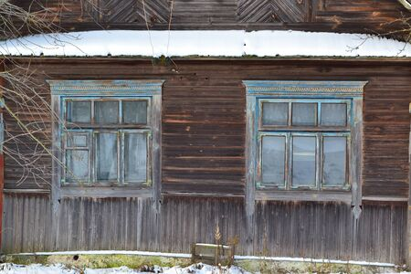 An old wooden window in russian style on a log wall.