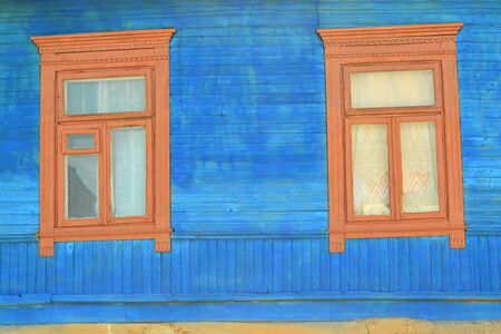 Old wooden windows on a log wall in bright blue. Decoration with carved clypeus. Old village