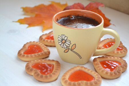Cookies in form of little heart and autumn maple leaf with coffee cup on old wooden table