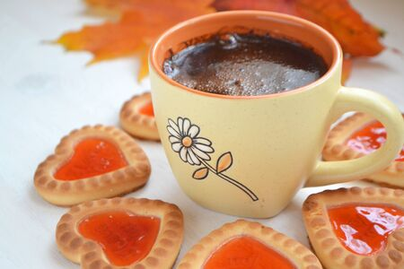 Orange cup of coffee with hearts cookies close up