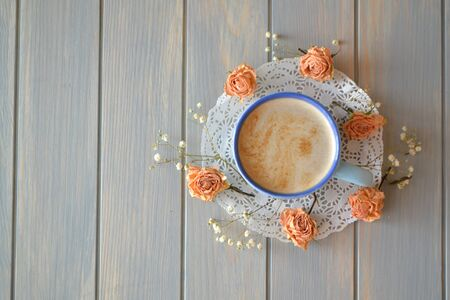Morning coffee or cappuccino and dry rose flowers on blue vintage table flat lay