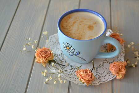 little cup of coffee with dry vintage beige roses on wooden plank table in blue and turquoise