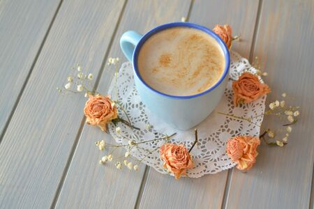 flowers of rose and cup of coffee are on a blue wooden plank surface, vintage style Stockfoto - 132600489