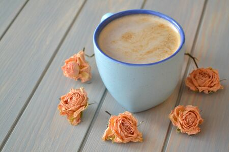 Coffee cup and dry roses in cremy color on blue vintage table, provence style Stockfoto - 132600923