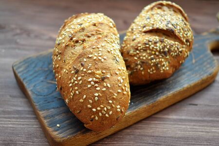 Two bread rolls sprinkled with seeds and caraway on rustic wooden table Stockfoto - 133081358