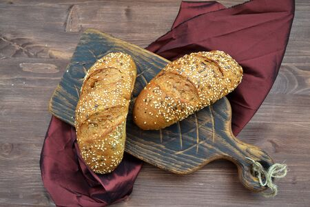 A sesame buns on a wooden cutting board and grenadine napkin on wooden table top view