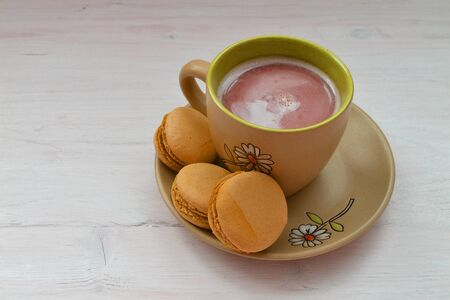 Orange macaron, macaroon and cup of coffee, shabby wooden background. Romantic morning Stockfoto