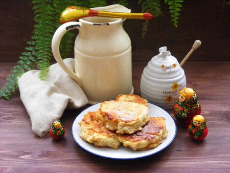 Traditional russian cuisine : crepes pancakes on plate with oak flakes on brown wooden background with rustic milk jug, honey and nesting dolls matrioshka Stockfoto - 133082180