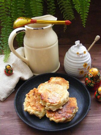 Russian cuisine : crepes pancakes with oak flakes on wooden background with rustic milk jug and nesting dolls matrioshka vertical photo Stockfoto - 133081491