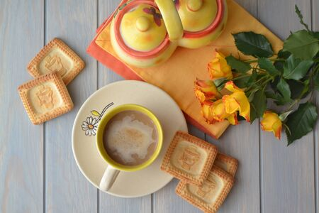 gentle breakfast concept: coffee, fresh cookies and yellow roses top view, teal wooden table