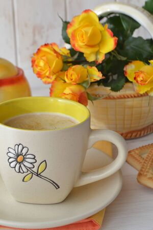 Hot latte coffee cup and beautiful yellow roses on shabby wooden background, vertical photo