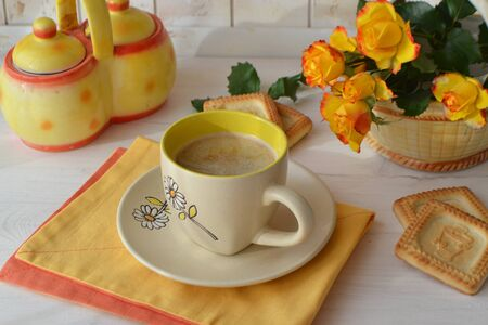 Bouquet or yellow and orange roses with mug or cup of coffee, tea or cappuccino. Concept of starting a working day, holiday