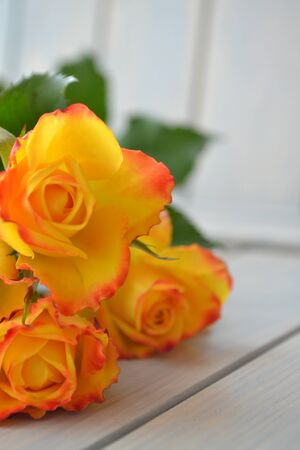 Yellow and orange roses flowers arranged on wooden background