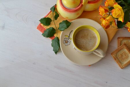 Cup of morning coffee, cappuccino and bouquet of yellow roses on wooden background, flatlay, top view. Space for text
