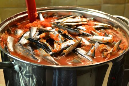 Preparation of russian conserved salade: fish in tomato sauce, in metal pan.