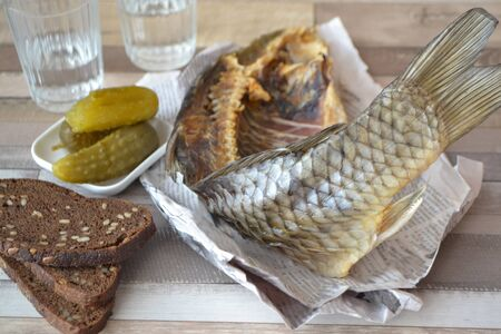 Conceptual image: vodka with a stockfish and newspaper with pickled cucumber and bread on an shabby background