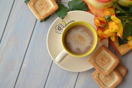 Hot coffee, yellow roses and homemade cookies in russian samovar on a blue wooden table with copy space. Top view image
