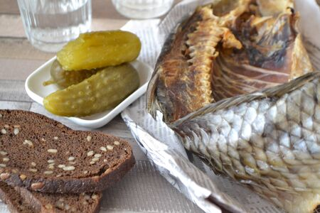Russian vodka with a stockfish and newspaper with pickled cucumbers and black bread