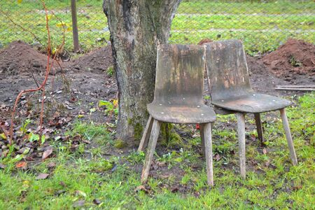 Two old wooden chairs in the shade of a tree in the autumn garden. Image of social problem