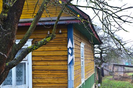 Fragment of old cracked country wooden house wall painted in yellow and blue, with windows, old village of Belarus Stockfoto