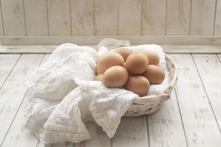 Organic brown chicken eggs from free-range farm in wicked rustic old basket