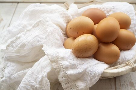 Organic brown chicken eggs in old rustic basket and vintage linen napkin Stockfoto