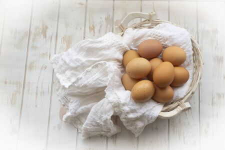 Organic farm eggs in wicked basket and linen napkin on rustic shabby table top view Stockfoto