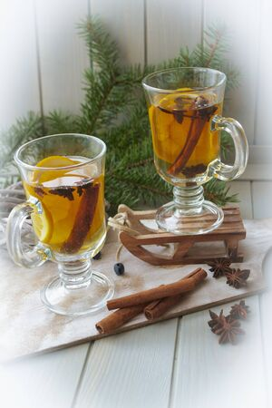Mulled wine with slice of orange and spices. Conceptual bright card in yellow, blue and white colors. Vertical image