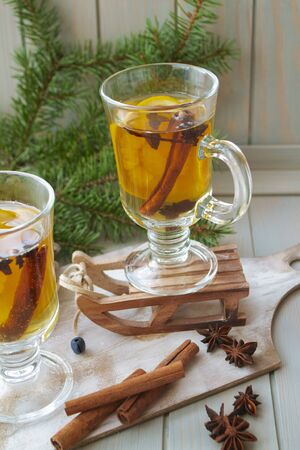 Hot mulled wine with Christmas spices and orange slices, anise and cinnamon sticks, vertical image