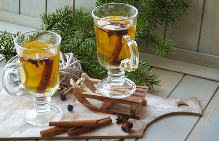 Mulled wine with Christmas spices and orange slices, anise and cinnamon sticks. Glass pubs with yellow drink on blue planks background and green spruce branch