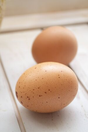 Close up of chicken eggs, fresh farm eggs over a rustic wooden table. Vertical image