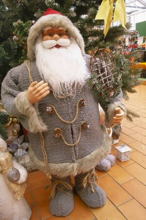 Leprechaun at the market, Christmas old traditional Santa Claus gnome in rustic style in grey and silver, with forest cones, vertical image